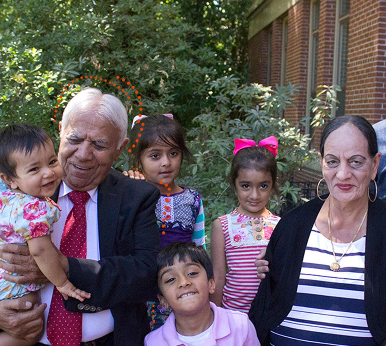 Satnam Sethi with grandchildren and wife standing in front of Kidder Hall