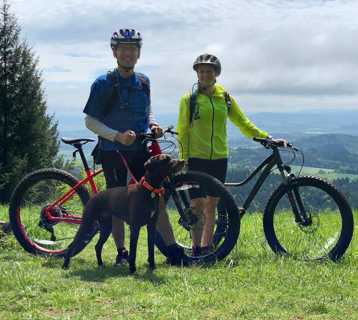 Courtney Rae Armour with husband and dog riding mountain bikes atop grassy hill