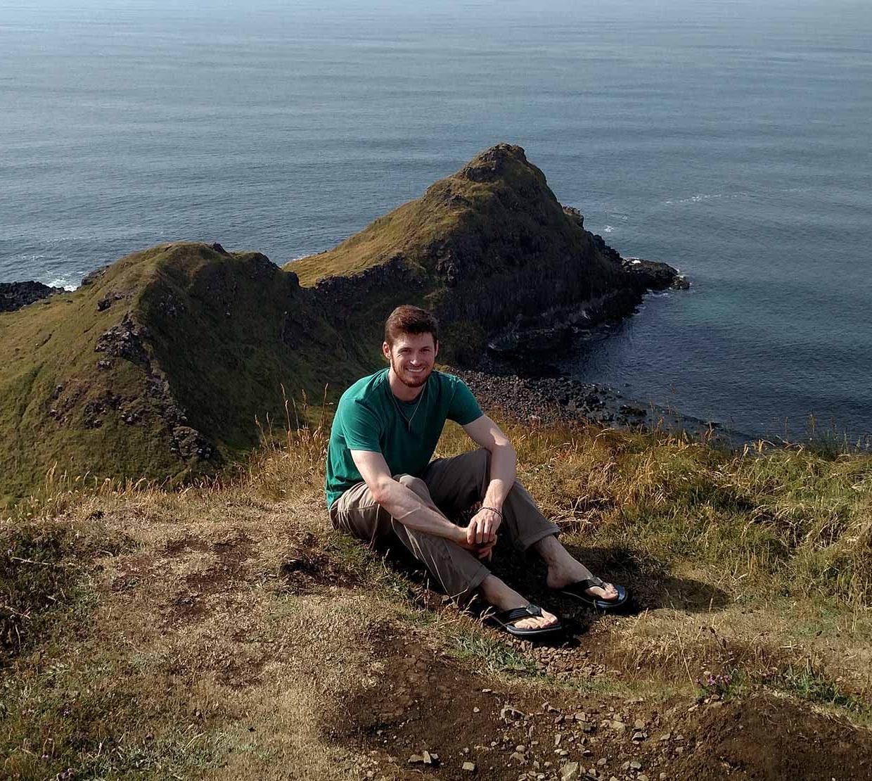 Nathan Jespersen sitting on an ocean viewpoint