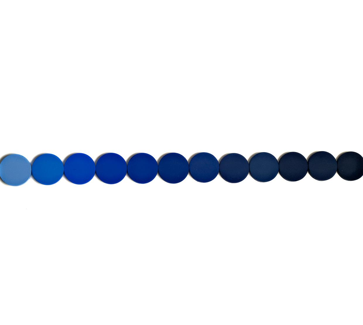 Blue pigment circles in a row on top of white backdrop