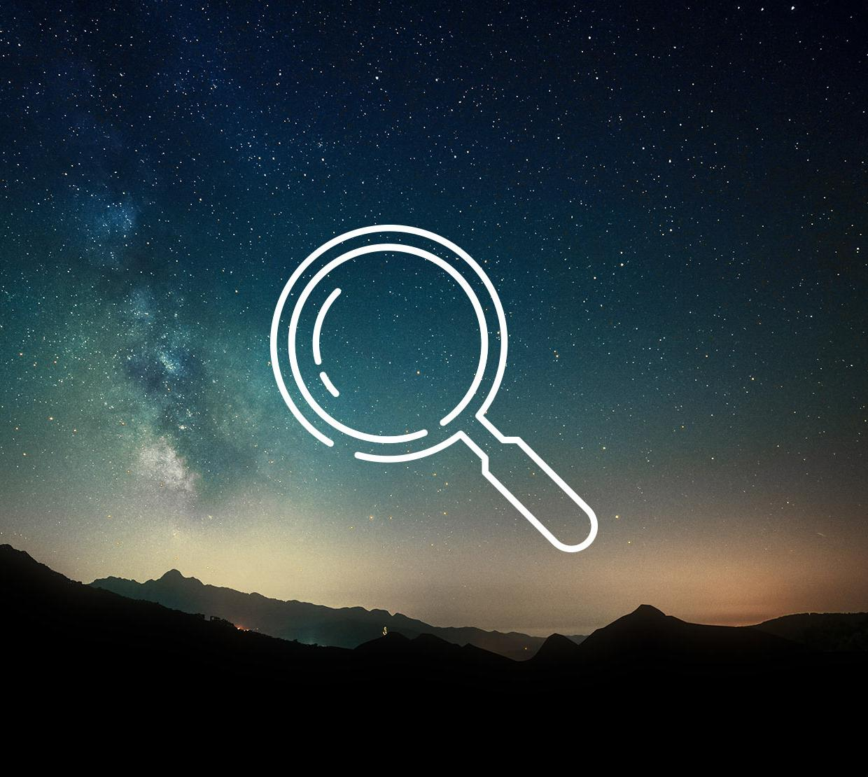 Magnifying glass icon above starry time lapse with mountain range