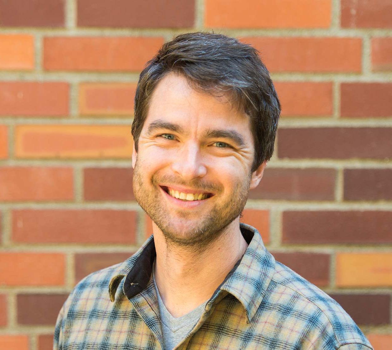 Benjamin Dalziel standing in front of brick wall