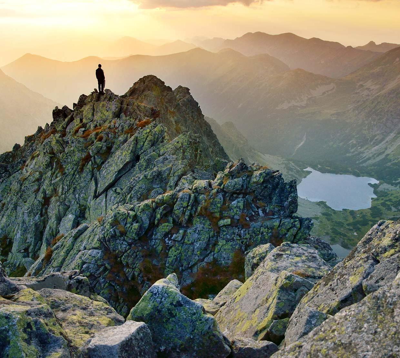 Person standing atop mountain in mountain range