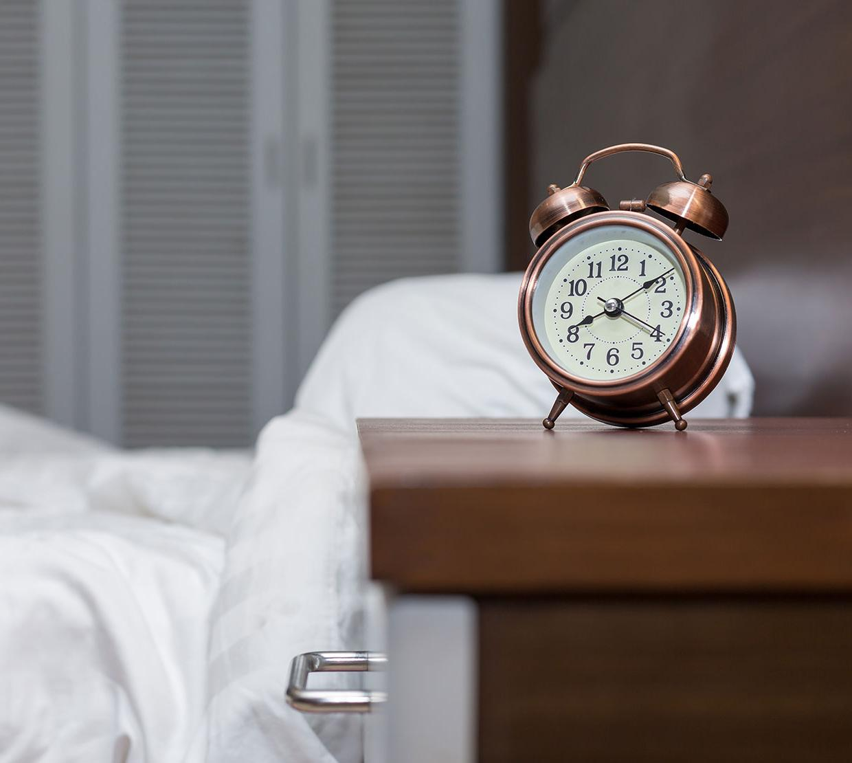clock sitting on nightstand next to bed