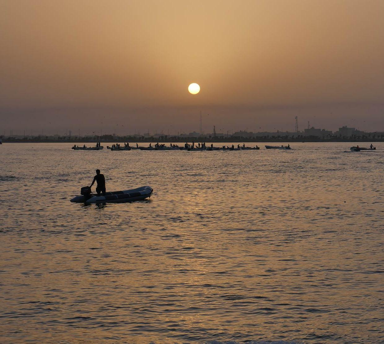 person riding small boat in ocean during sunset