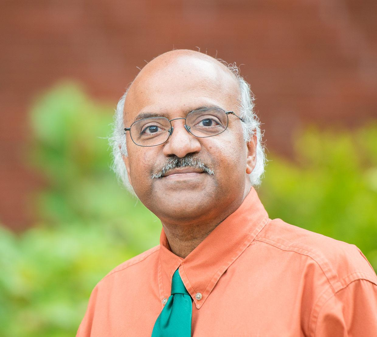 Sastry Pantula standing in front of shrubbery and brick wall