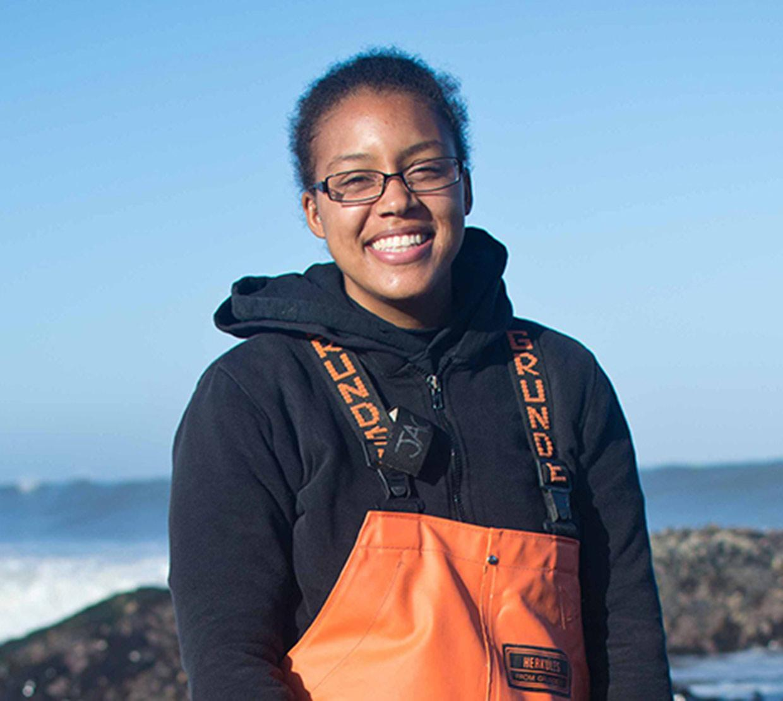 Courtney Jackson standing in rocks next to ocean shore