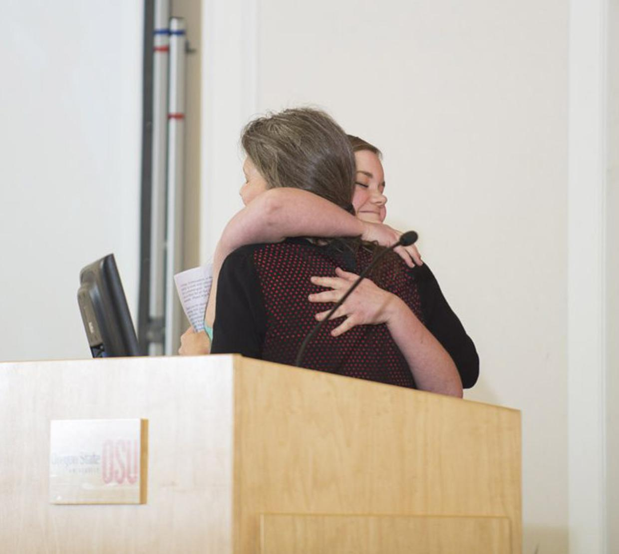 Two women hugging each other behind podium