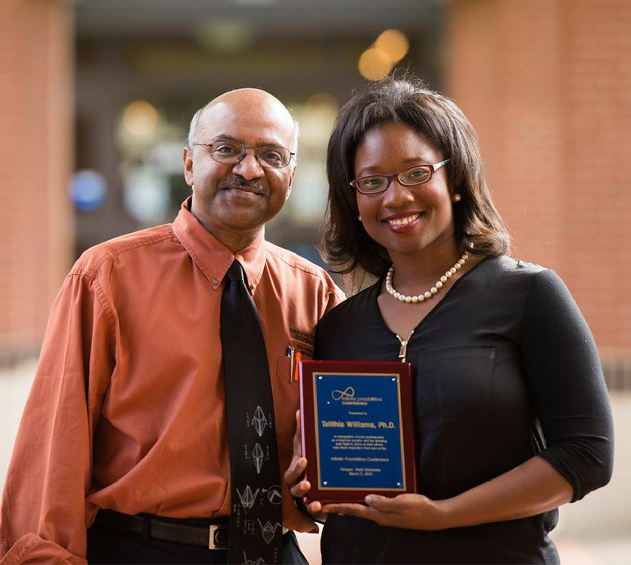 Talithia Williams receiving award from Sastry Pantula