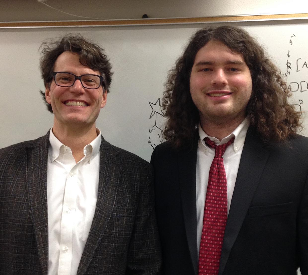 Ryan Mehl and Robert J Blizzard standing in front of white board in suits