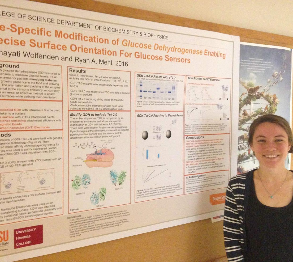 Hayati Wolfenden standing next to her research poster