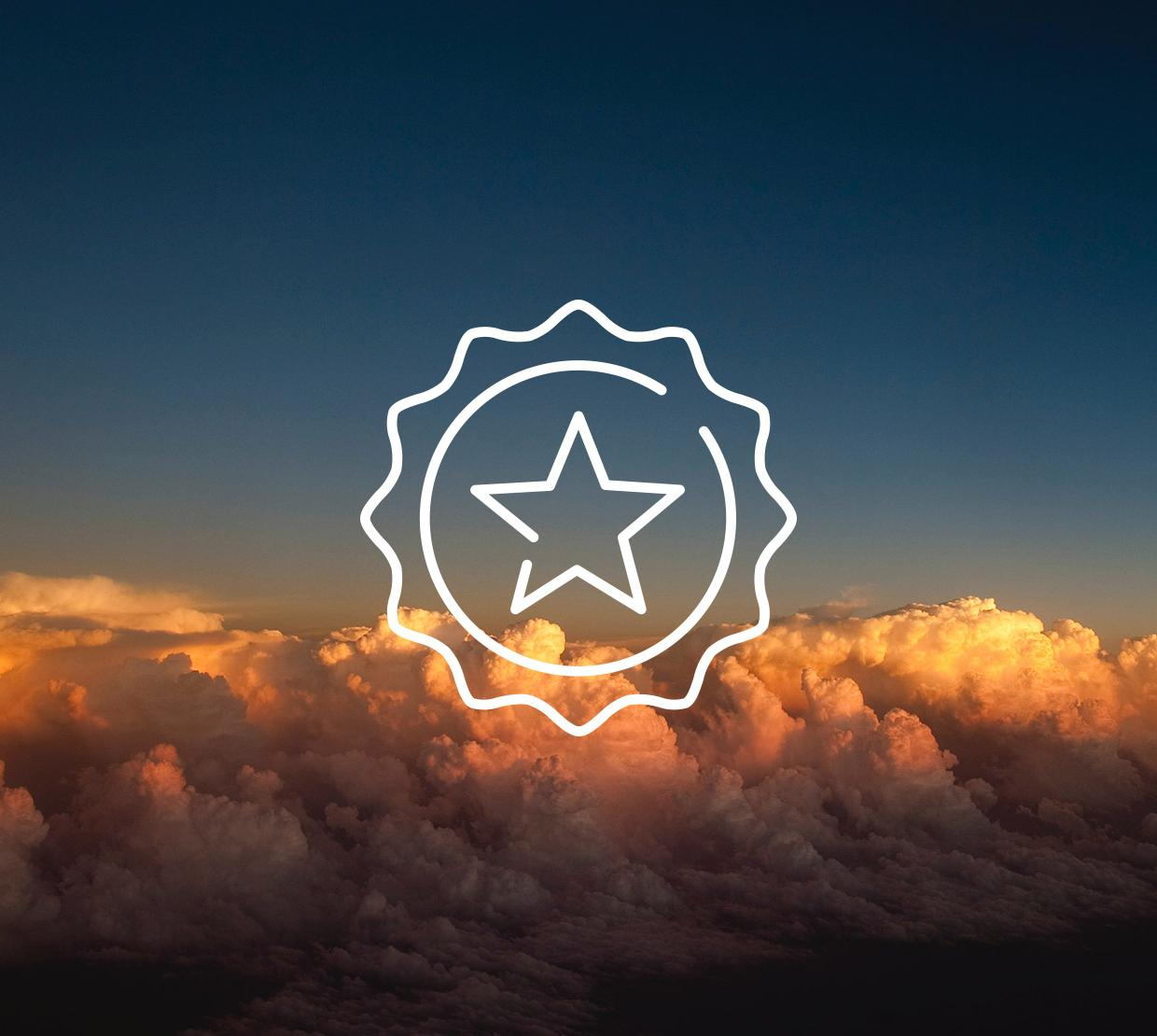 Star icon above clouds at sunset