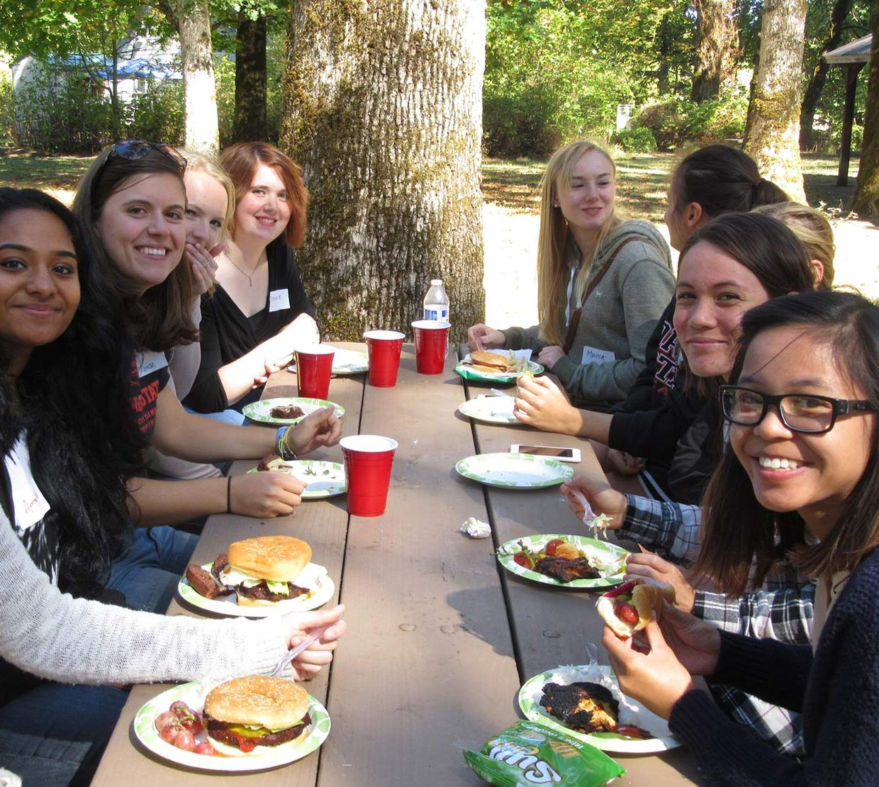 students sitting around picnic table eating lunch