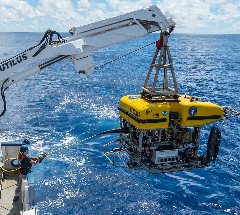 boat crane releasing research submarine into ocean