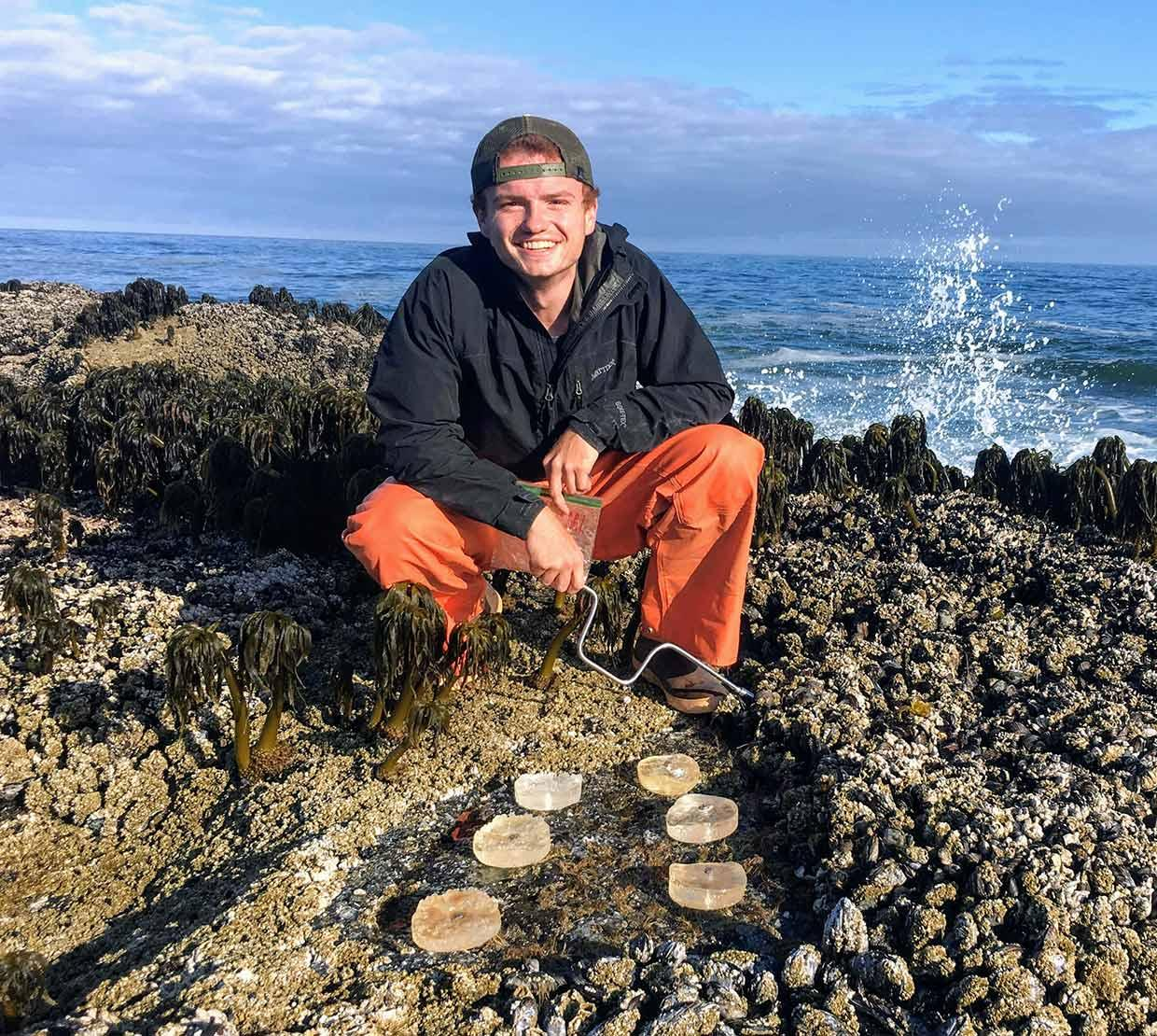 Kristofer Bauer standing on rocks on ocean shore with research equipment
