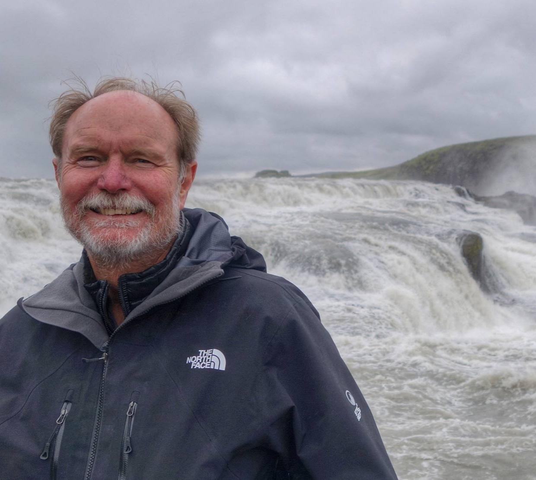 Joel Peterson standing in front of waterfall
