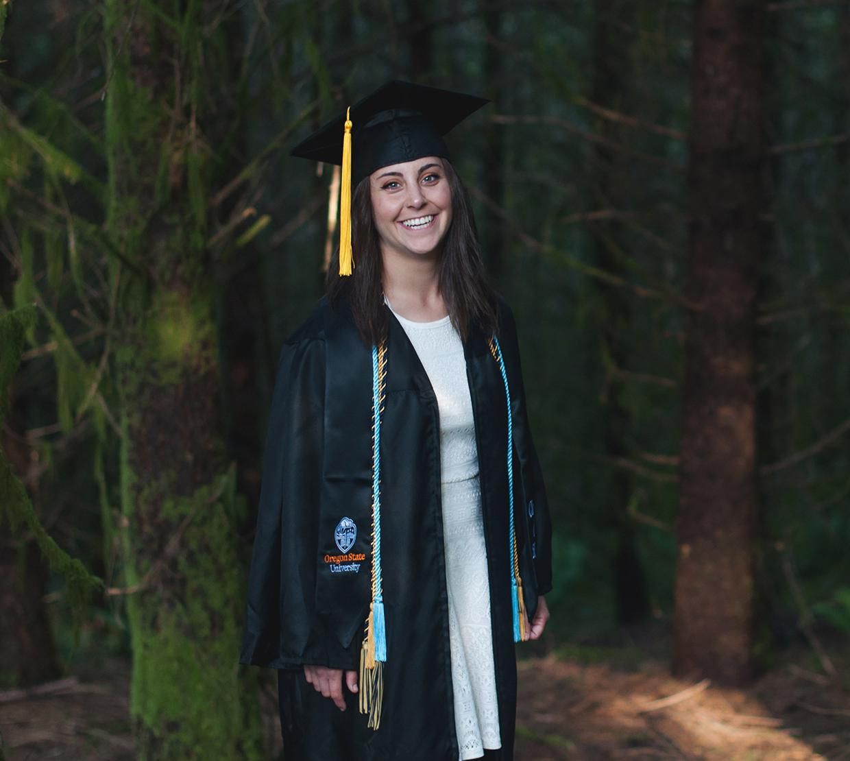 Taylor Robinson in graduation gown, standing in forest