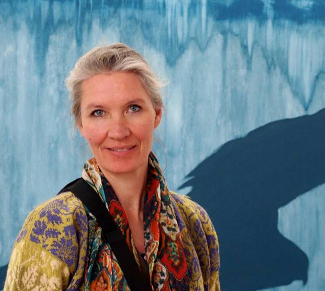 Mai Gehrke in front of blue painted backdrop