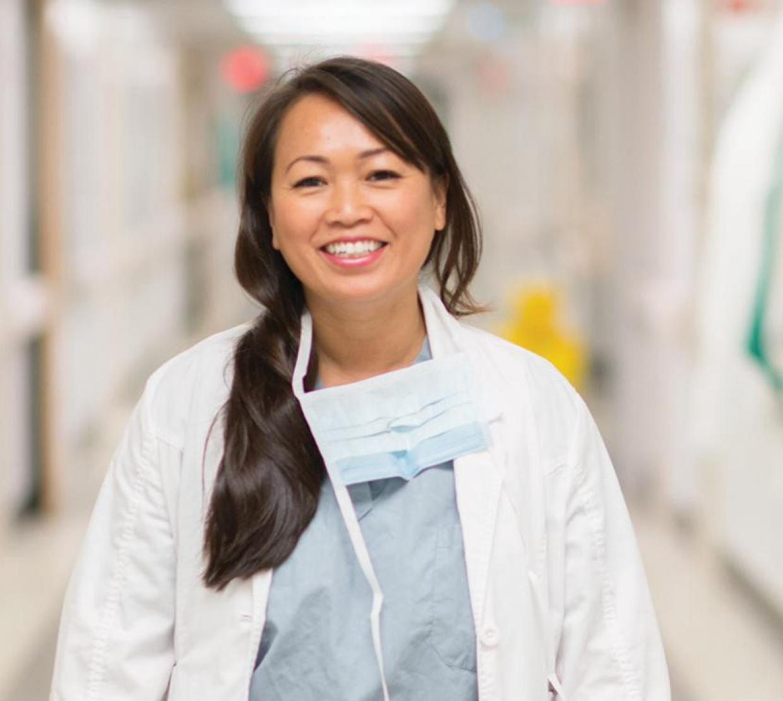 Dr. SreyRam Kuy wearing scrubs in hospital hallway
