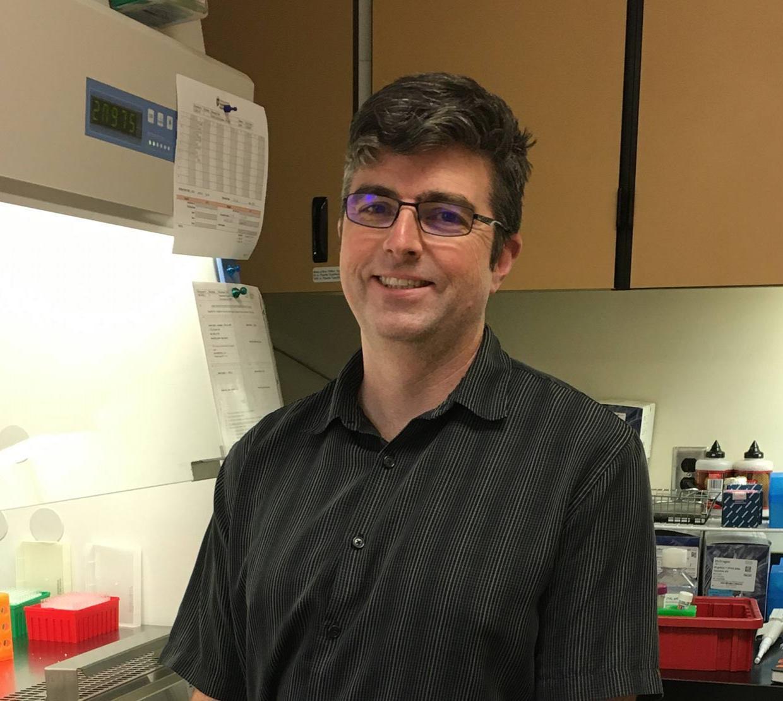 Justin Sanders sitting in lab