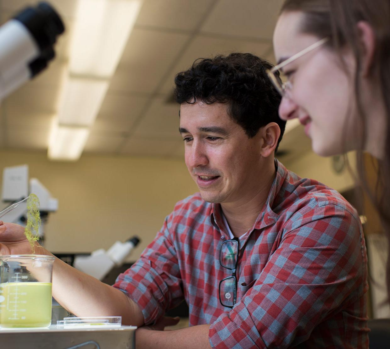 Felipe Barreto looking at lab samples with student