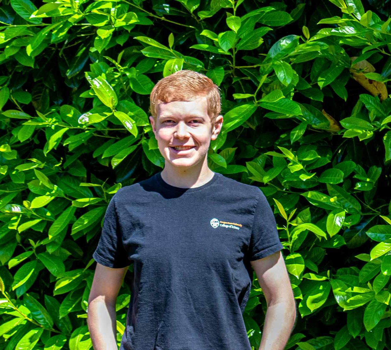 Mathew Frischman standing in front of a green bush