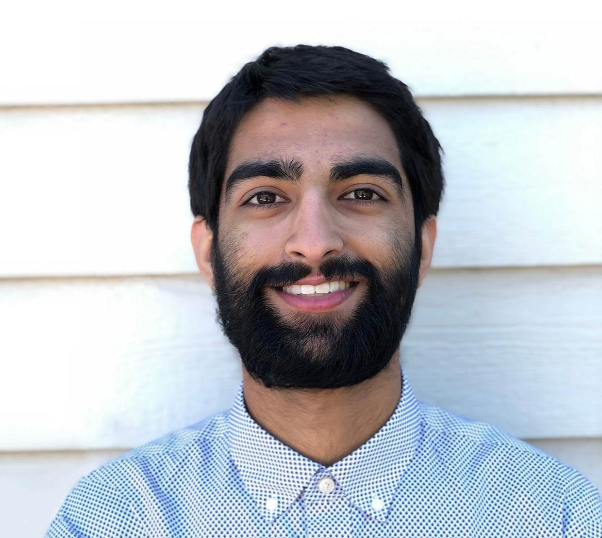 Mahtab Brar smiles in front of a background of white siding.