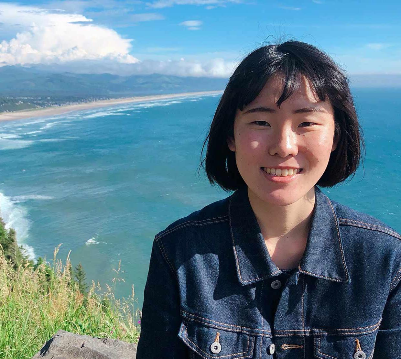 Mai Sakuragi in front of a coastal view