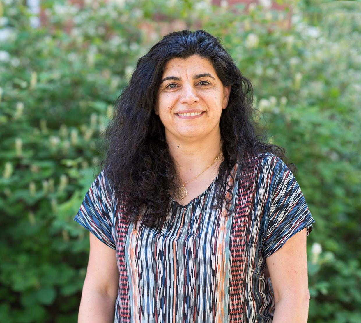 Elisar Barbar standing in front of a green background