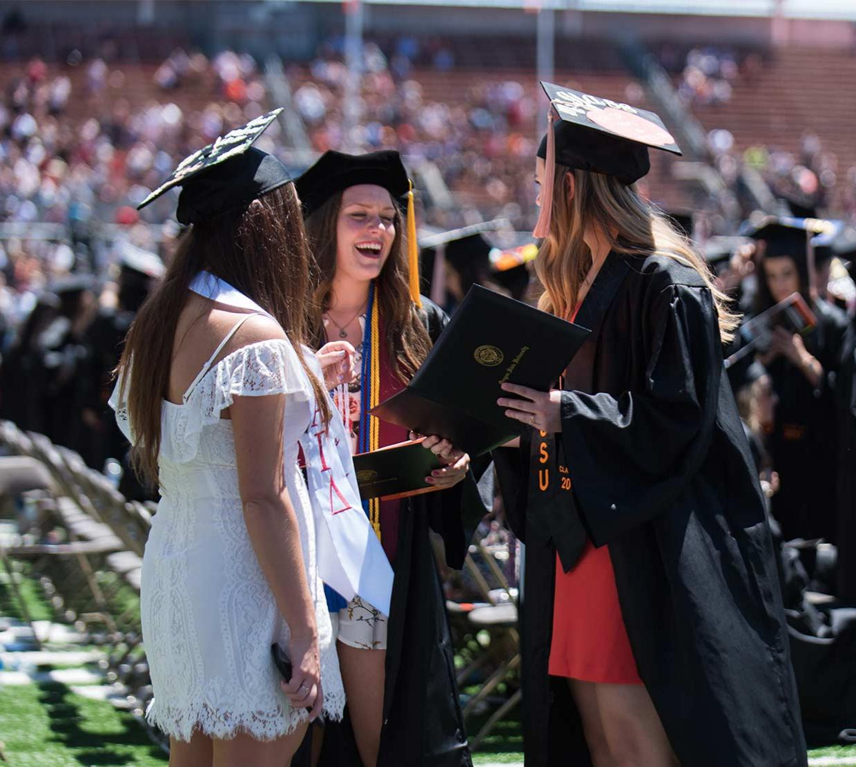 Three graduates smile together during graduation.