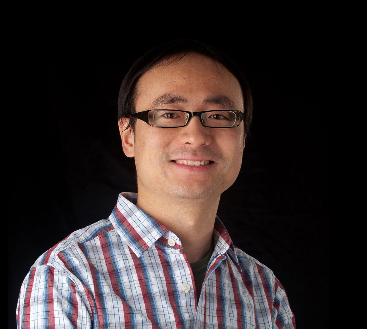 Chong Fang, standing in front of black backdrop
