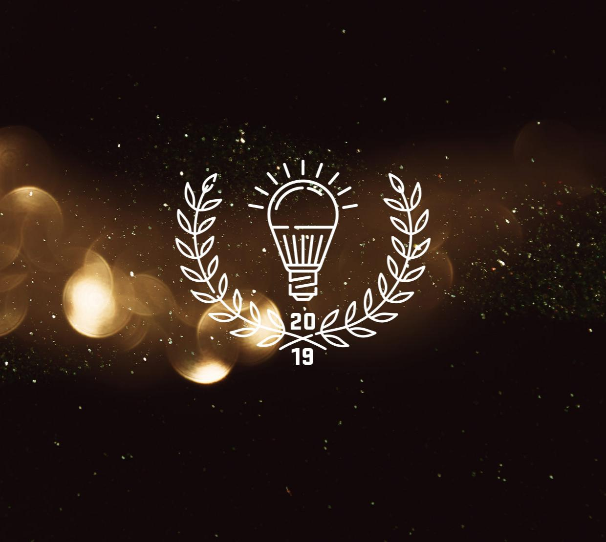 "Light bulb and laurel icon labeled ""2019"" above light texture"