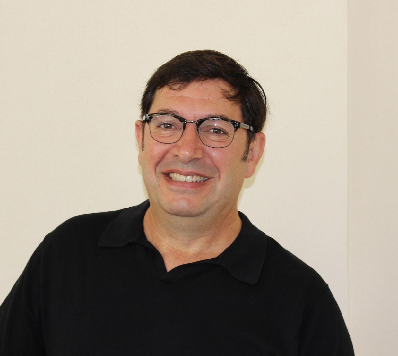 Juan Restrepo sitting in front of beige backdrop