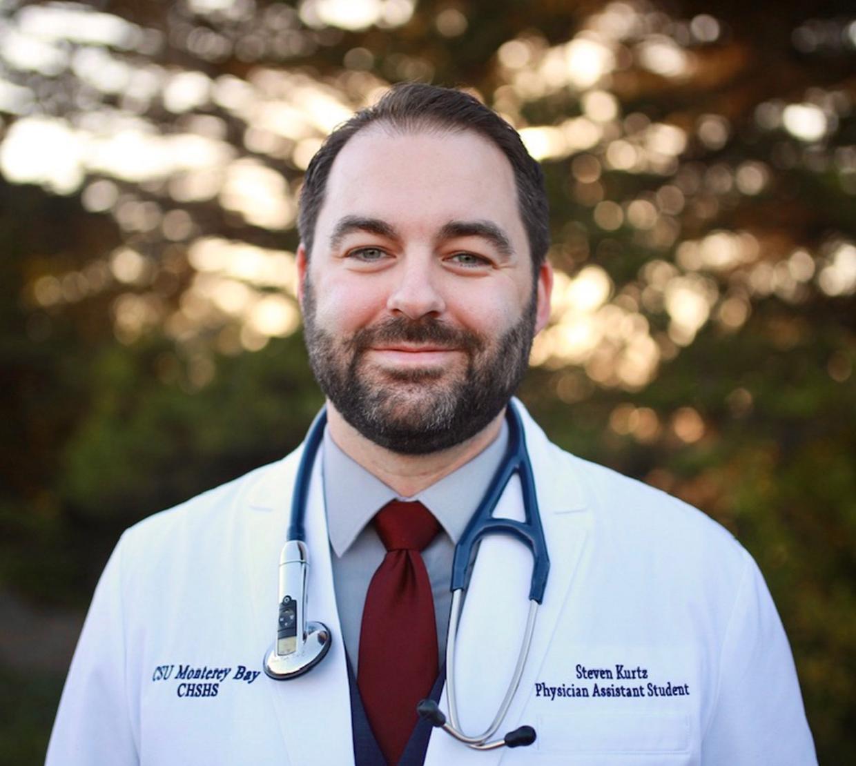 Steven Kurtz in a doctor coat and stethoscope