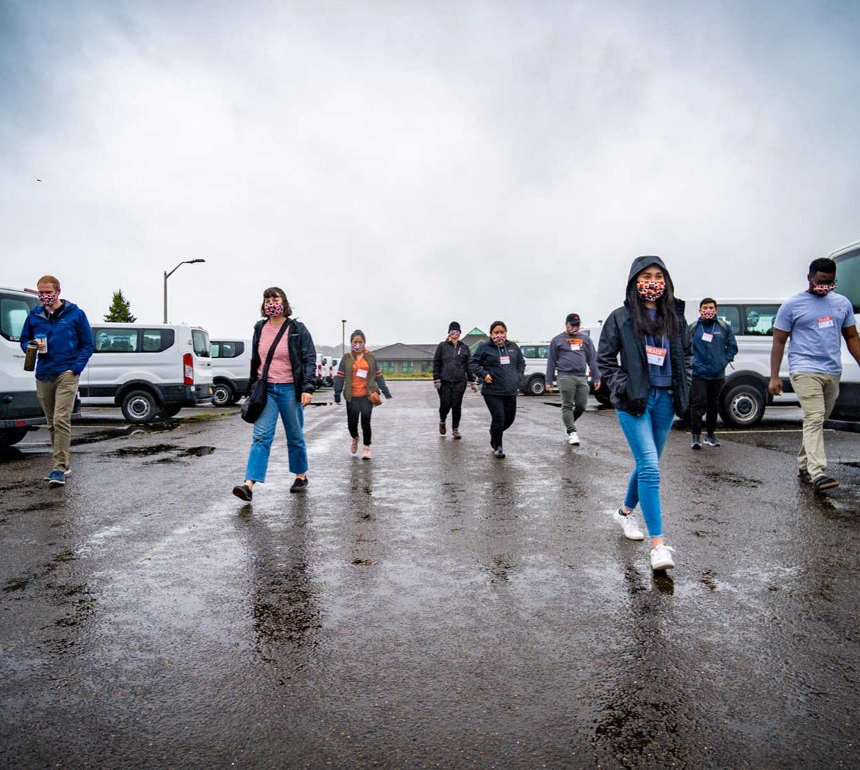 TRACE field staff walking along parking lot in Newport, Oregon on a cloudy and rainy day.