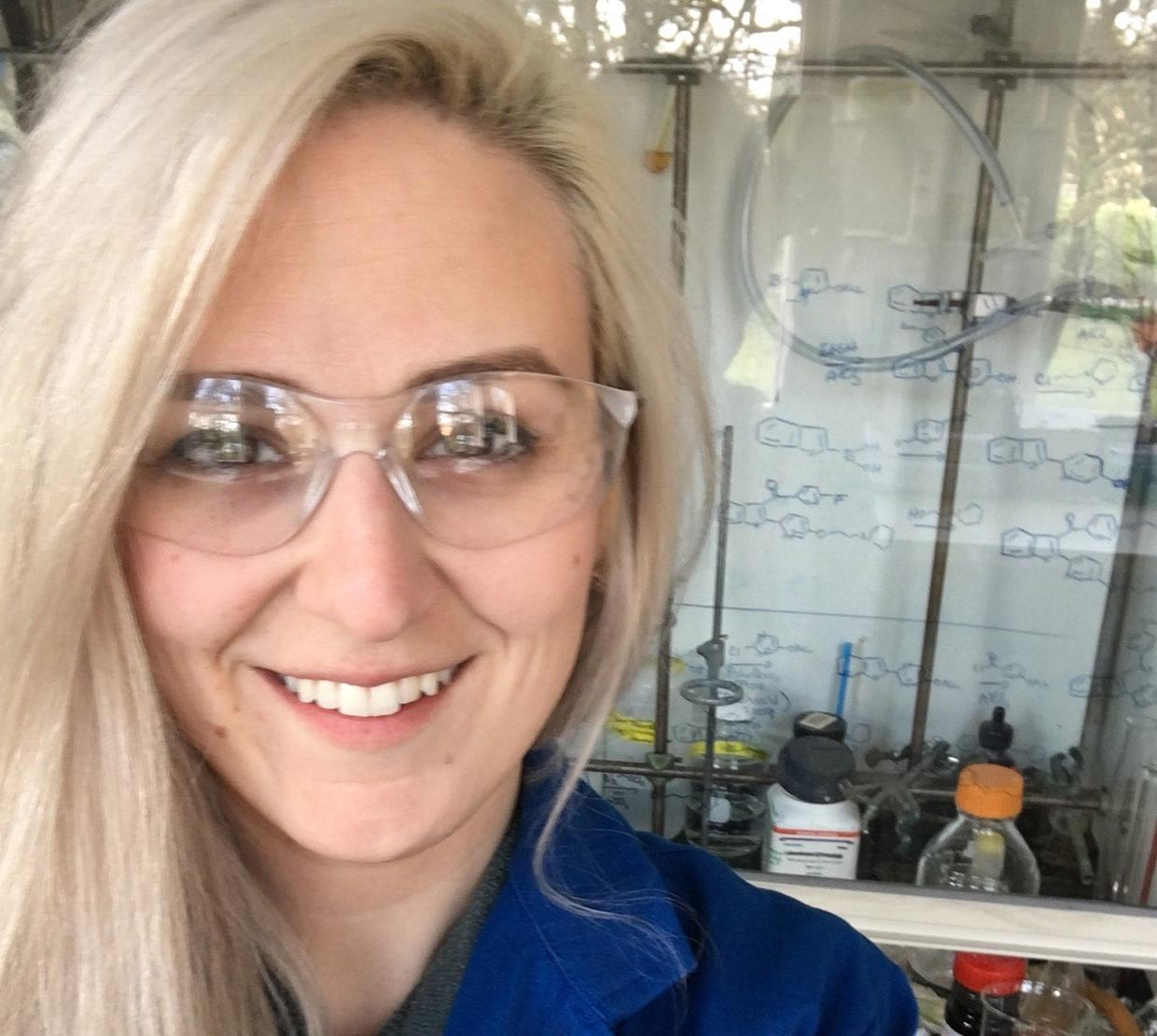 Blonde woman with clear eye protection smiling in a laboratory setting