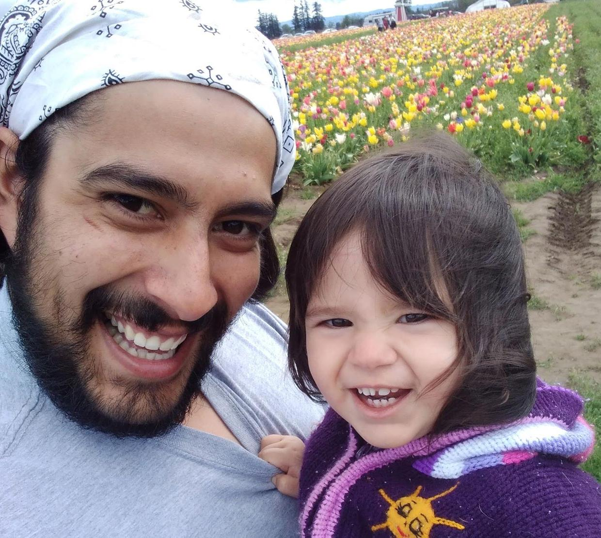 Oregon State physics graduate with daughter amid tulips.