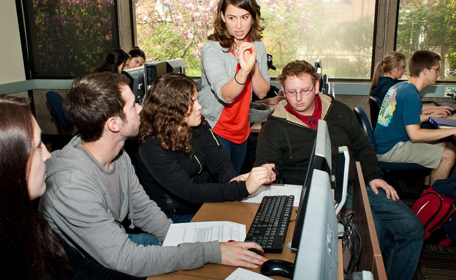 professor helping students in computer lab