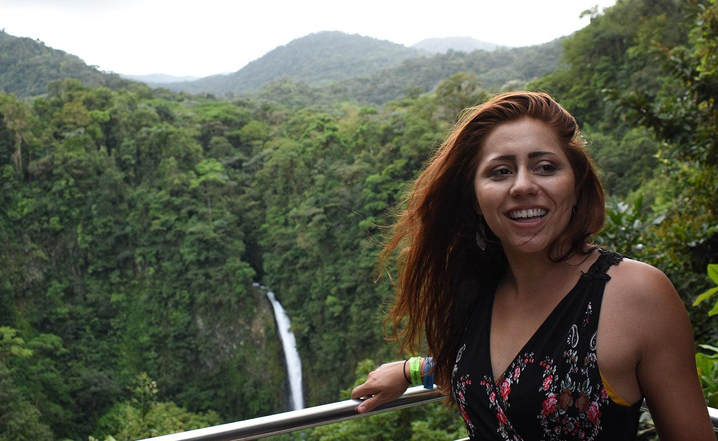 Tonya Allison in front of waterfall in tropical forest