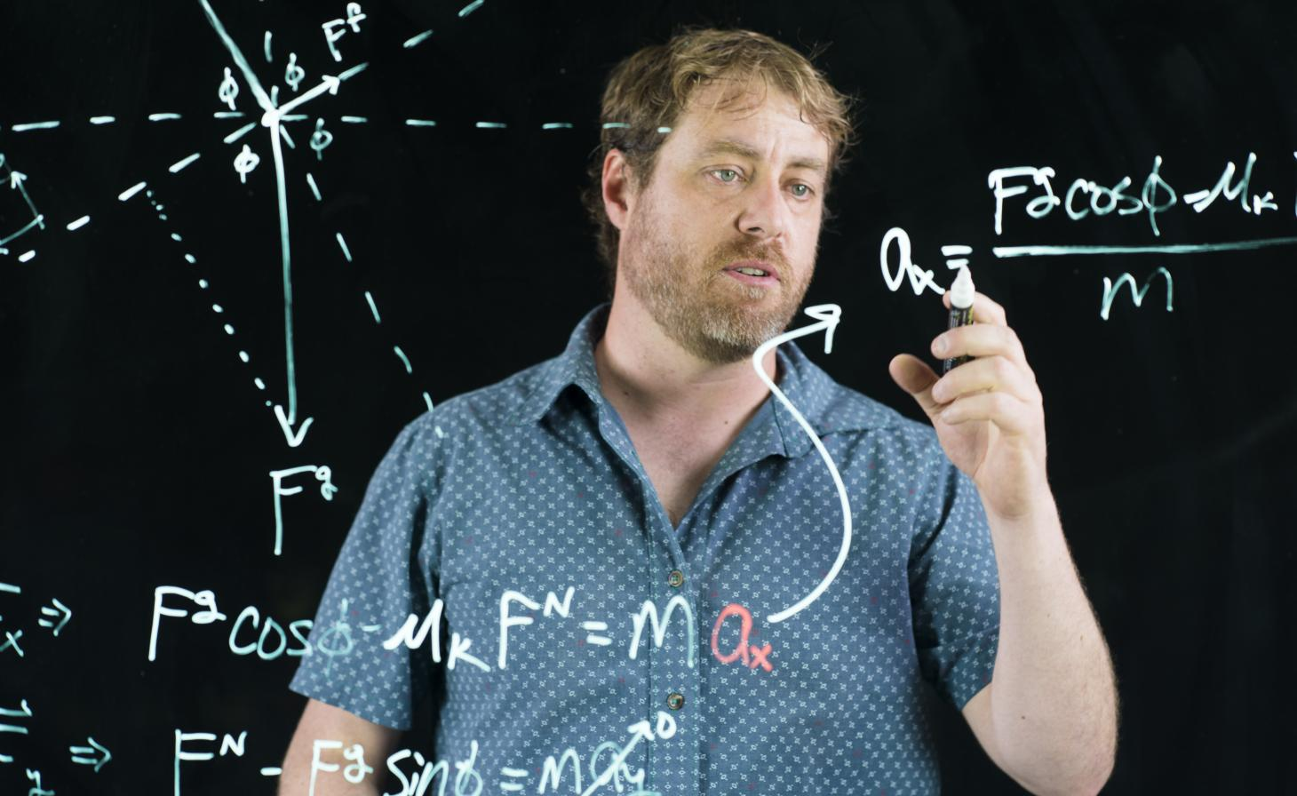 KC Walsh writing equation on translucent board in front of black backdrop