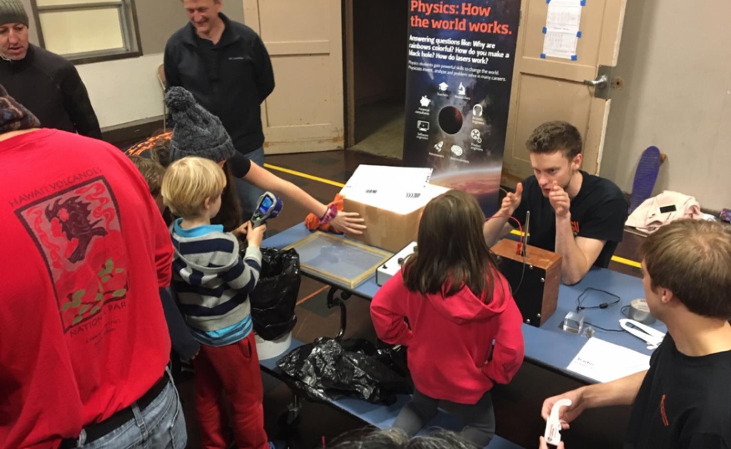 Science students teaching elementary school children