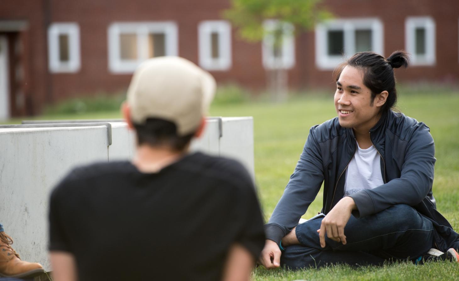 students sitting on Austin Hall lawn