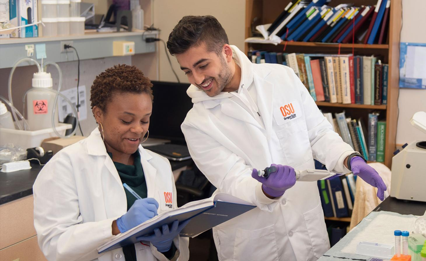 Graduate students working together in lab.