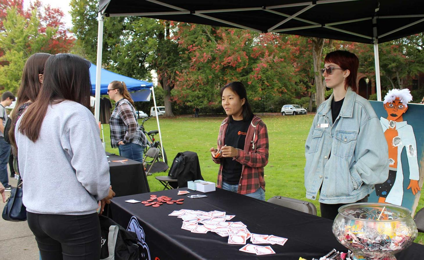 Peer advisors talking with students at College of Science booth in Memorial Union quad.