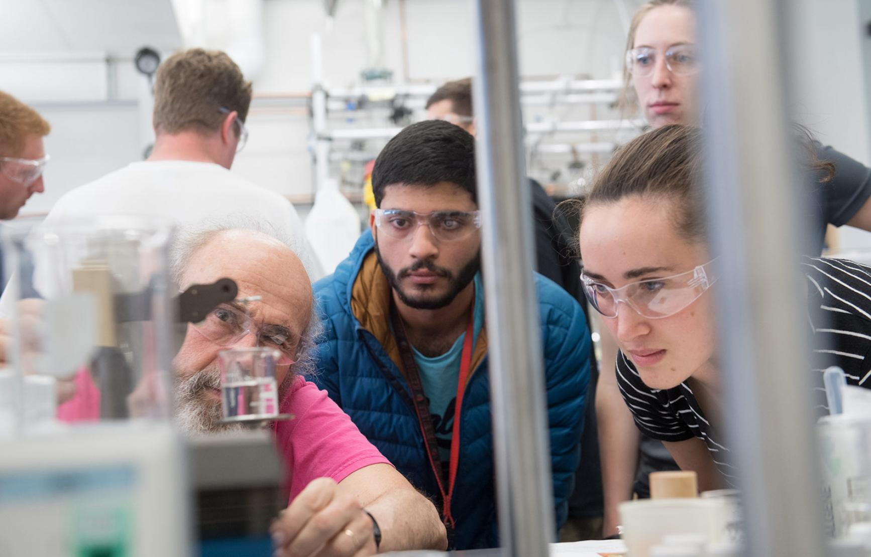 Science students with professor looking at experiment in lab