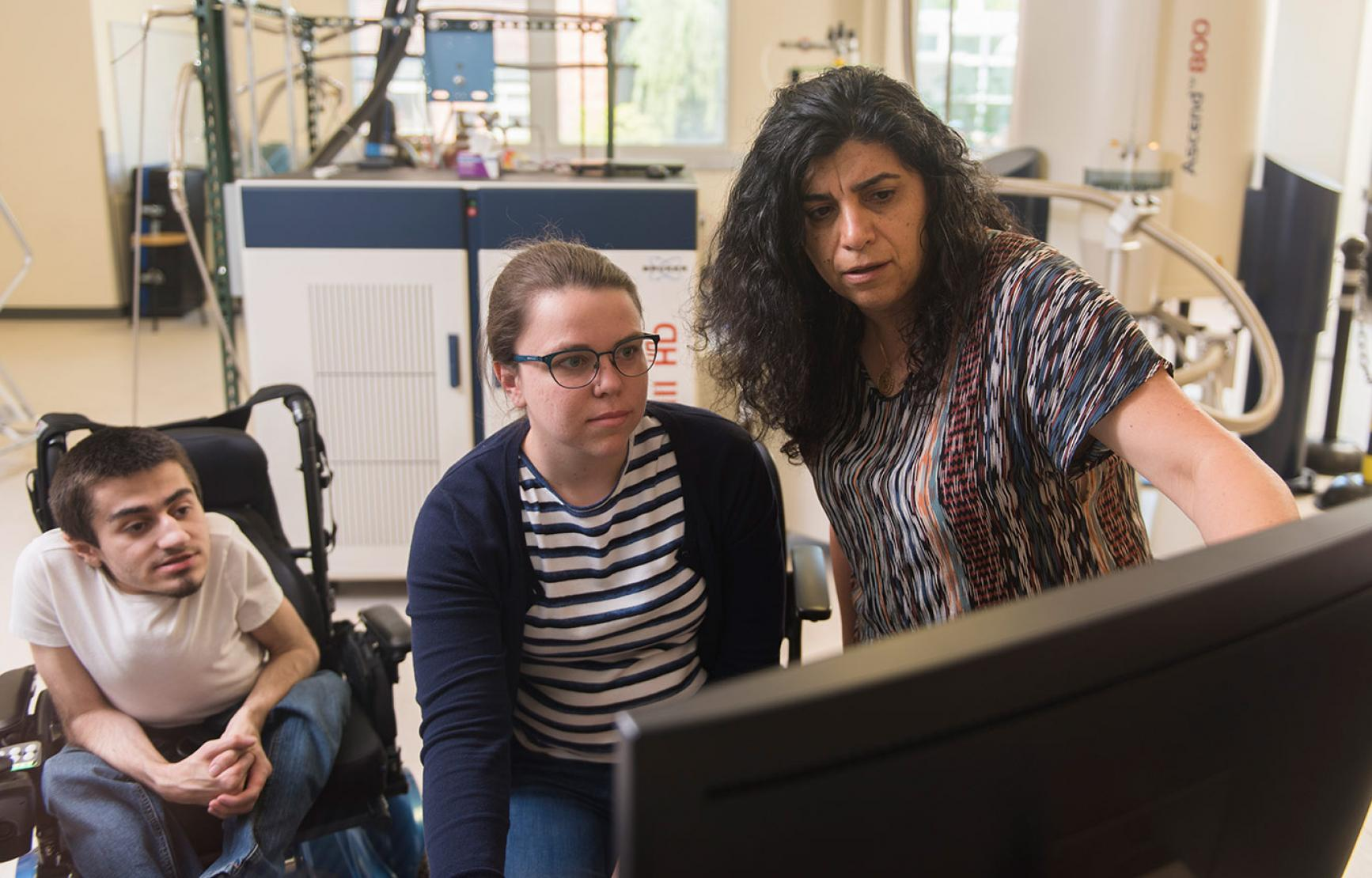 Elisar Barbar analyzing data with graduate students in lab