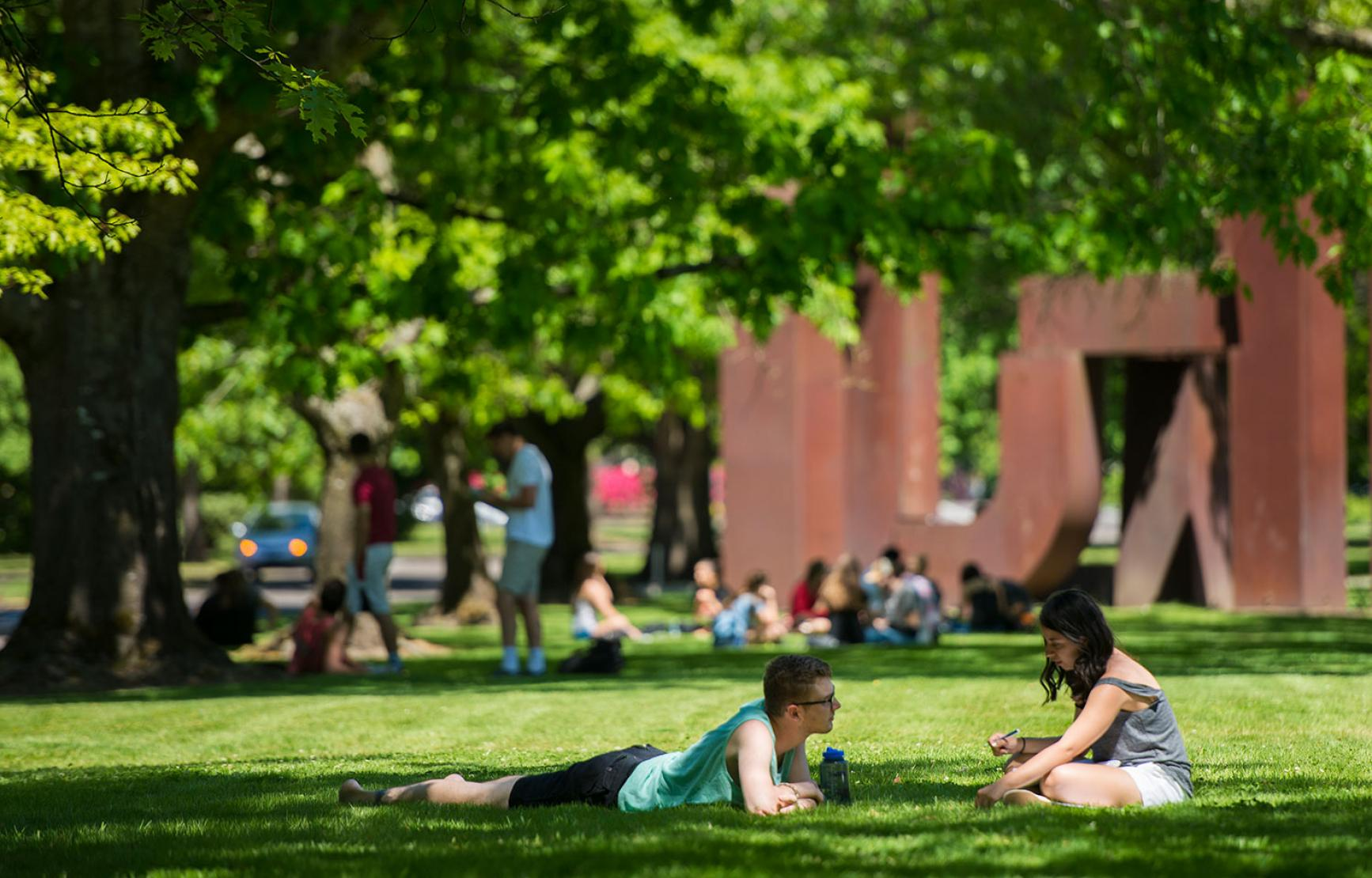 Students sitting outside West Hall lawn