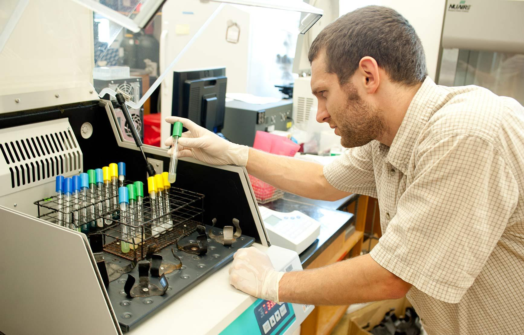 male student working with equipment in the Schuster Lab