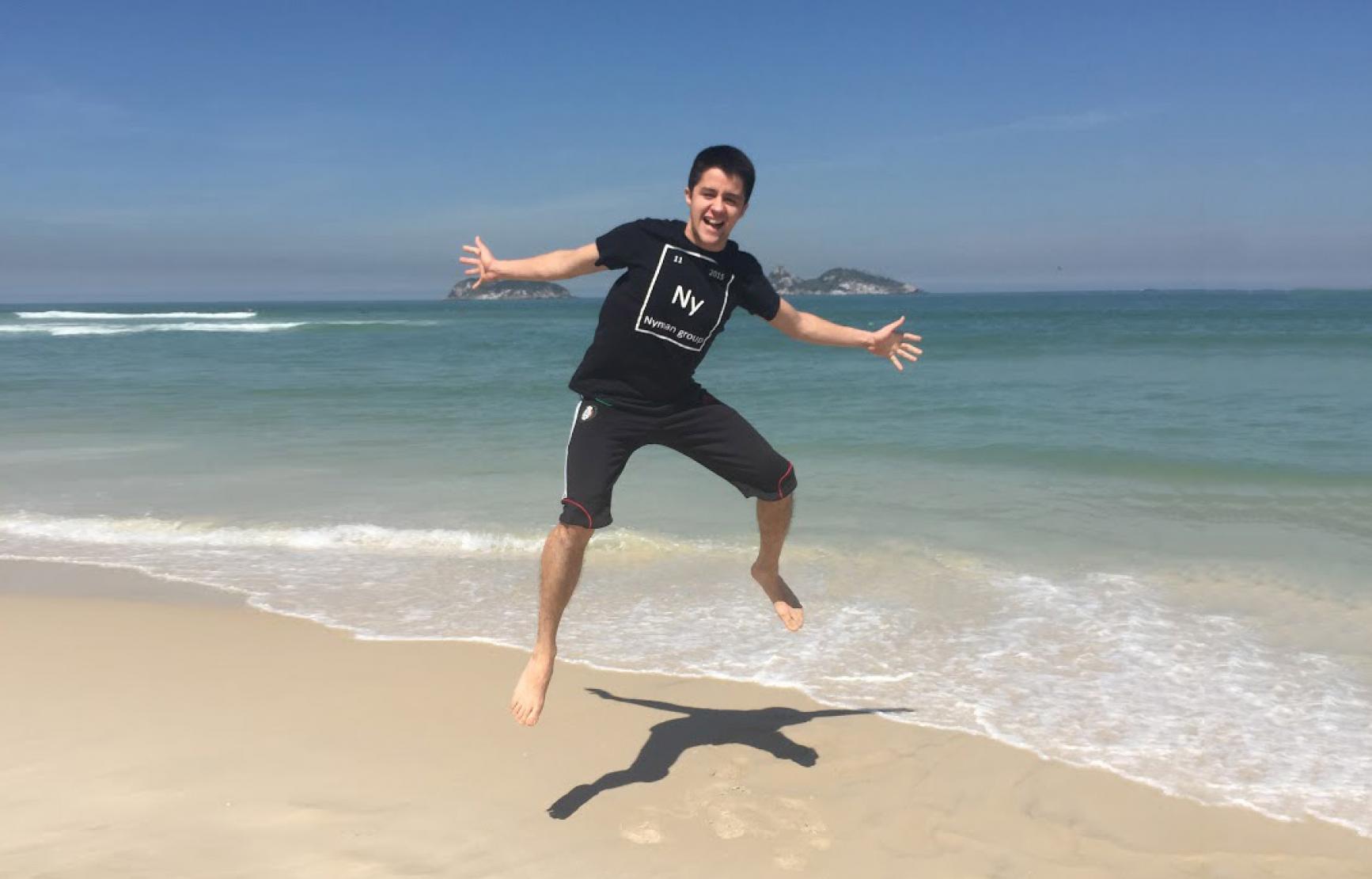 Collin Muniz wearing a chemistry t-shirt jumping on the beach