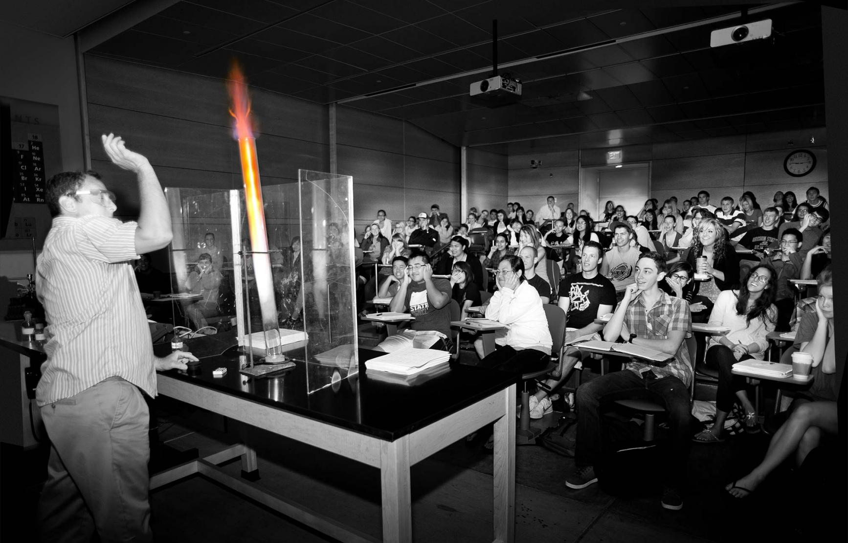 black and white photo of Richard Nafshun lighting fire in lecture demo